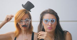Two young woman with carnival masks on sticks. Portrait of two funny young woman with carnival masks on sticks kidding on white background stock video