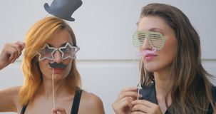 Two young woman with carnival masks on sticks. Portrait of two funny young woman with carnival masks on sticks kidding on white background stock footage