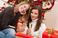 Two young woman with champagne on Christmas Royalty Free Stock Photos