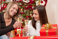 Two young woman with champagne and Christmas tree Royalty Free Stock Images