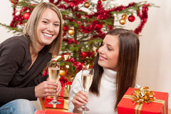Two young woman with champagne and Christmas tree Royalty Free Stock Photo