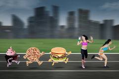 Two Young Woman Chased by Junk Food Royalty Free Stock Photos