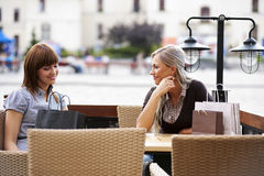 Two young woman chatting. Two beautiful and sophisticated young women friends sitting in a cafe outdoor Stock Photos
