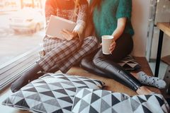 Two young woman chatting in a coffee shop. Two friends enjoying coffee together. One girl uses a tablet. Two young women chatting in a coffee shop. Two friends Stock Images