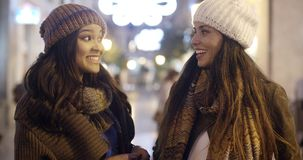 Two young woman chatting outdoors in winter. Two stylish attractive young woman chatting outdoors in winter standing in a brightly lit urban street at night stock footage