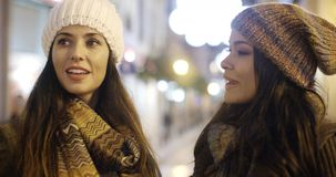 Two young woman chatting outdoors in winter. Two stylish attractive young woman chatting outdoors in winter standing in a brightly lit urban street at night stock video footage