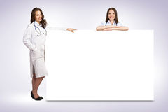 Two young woman doctor holding a blank banner Royalty Free Stock Images