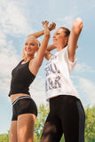 Two young woman doing sports outdoors in a park on sunny summer Stock Image