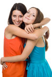 Two young woman embrace and smile royalty free stock image
