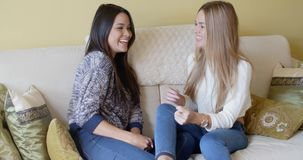 Two young woman enjoying a chat. As they laugh and smile together while relaxing on a sofa at home stock video footage