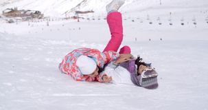 Two young woman enjoying a frolic in the snow. Two young woman in stylish ski clothes enjoying a frolic in the snow on a mountain slope overlooking a ski lift at stock video