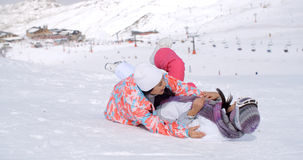 Two young woman enjoying a frolic in the snow. Two young women in stylish ski clothes enjoying a frolic in the snow on a mountain slope overlooking a ski lift at Royalty Free Stock Photo