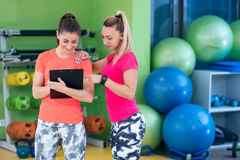 Two young woman enjoying their exercise routine at the gym laughing and smiling Stock Images