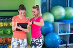 Two young woman enjoying their exercise routine at the gym laughing and smiling Royalty Free Stock Photography