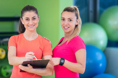 Two young woman enjoying their exercise routine at the gym laughing and smiling Stock Photography