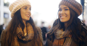 Two young woman enjoying a winter night out. Two young women enjoying a winter night out together as they stand chatting in a brightly lit urban street in trendy Stock Photo