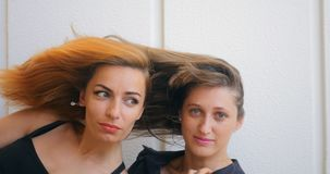 Two young woman with flying hair. Portrait of two young funny woman with flying hair stock video