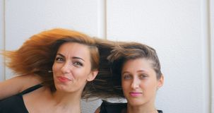 Two young woman with flying hair. Portrait of two young woman with flying hair seriously standing on white background stock footage