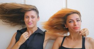 Two young woman with flying hair. Portrait of two funny young woman with flying hair stock video footage