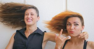 Two young woman with flying hair. Portrait of two funny young woman with flying kidding on white background stock video footage