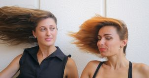Two young woman with flying hair. Portrait of two funny young woman with flying kidding on white background. Woman with red hair appears from down side stock footage