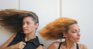 Two young woman with flying hair. Portrait of two young woman with flying hair looking firstly in opposite directions, then to each other stock video footage