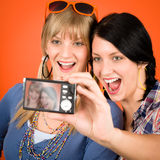 Two young woman friends taking picture smiling. Two young women friends taking picture with camera orange background Stock Image
