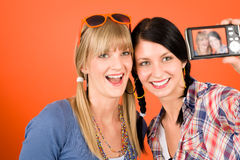 Two young woman friends taking picture smiling. Two young women friends taking picture with camera orange background Stock Images