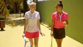 Two young woman friends at the tennis club. Walking along carrying their rackets and chatting stock video footage