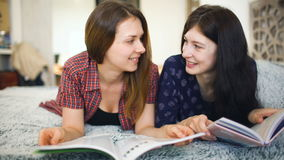 Two young woman friends are watching magazine on bed in bedroom at home. Two female friends are watching magazine on bed at home stock video footage