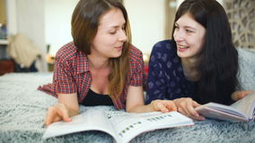 Two young woman friends are watching magazine on bed in bedroom at home stock video footage