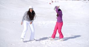 Two young woman frolicking in winter snow. Two young woman frolicking in fresh deep white winter snow at a mountain resort enjoying the fresh air and sunshine stock footage