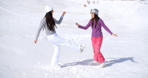 Two young woman frolicking in winter snow. Two young women frolicking in fresh deep white winter snow at a mountain resort enjoying the fresh air and sunshine Stock Photo