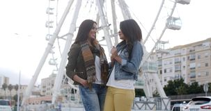 Two young woman in front of a ferris wheel. Two attractive trendy casual young woman standing chatting in front of a ferris wheel in an urban square  three stock video footage