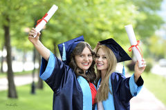 Two young woman graduate Stock Images