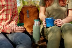 Two young woman hikers stopping for a drink. From a flask seated with a backpack between them and mugs in their hands in a close up view Royalty Free Stock Image