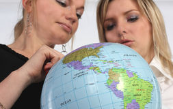 Two young woman holding a Globe Royalty Free Stock Images