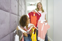 Two young woman holding up racks of clothes in corridor of change rooms in shop, smiling Stock Photos