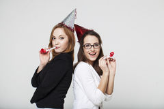 Two young woman in jackets on party. Two young women in jackets on party with party cones Stock Photos