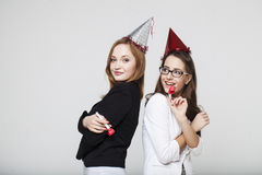 Two young woman in jackets on party. Two young women in jackets on party with cones Royalty Free Stock Photos