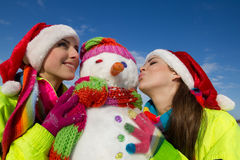 Two young woman kissing a snowman Royalty Free Stock Images