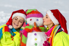 Two young woman kissing a snowman Stock Image