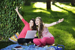 Two young woman with the laptop. A beautiful college students working on her laptop on campus. looking at camera surprised Royalty Free Stock Photography
