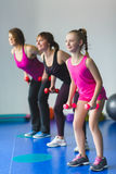 Two young woman and little girl doing gymnastic exercises. Instructor or Mother with daughter doing gymnastic exercises Royalty Free Stock Photo