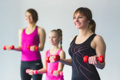 Two young woman and little girl doing gymnastic exercises. Instructor or Mother with daughter doing gymnastic exercises Stock Photo