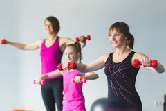 Two young woman and little girl doing gymnastic exercises. Instructor or Mother with daughter doing gymnastic exercises Stock Image