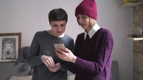 Two young woman looking mobile phone standing in room. Woman holding smartphone. Two young woman looking at mobile phone standing in room. Portrait of woman stock video footage