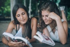 Two young woman lying in swing on beach, reading books. Two young women lying in swing on beach, reading books. Koh Tao, Thailand stock images