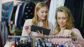 Two young woman make purchases in a clothing store. Enjoy your tablet, look things in the catalog and on the store. Stands. HD video stock footage