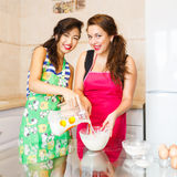 Two young woman making a pancakes royalty free stock photos